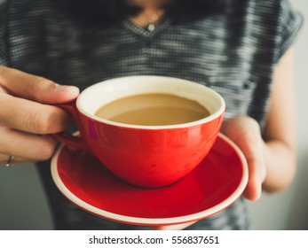 Woman hold red cup of  coffee in hand in soft morning light.