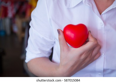 woman hold red heart and wearing white shirt blur background