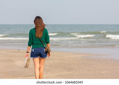 woman hold up shoes and walk on the beach