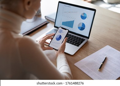 Woman hold smartphone use pc at workplace. Project stats financial data sales charts on laptop and cellphone screen, close up view over shoulder. Report preparation, synchronization for safety concept