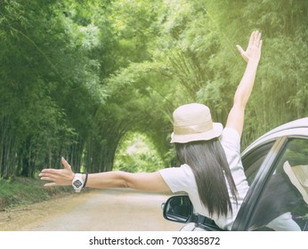 Woman hold up traveler sitting in car vintage tone