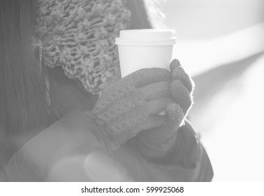 Woman hold warming coffee drink in hands.Girl in warm winter clothes holding white paper take away coffee cup.Place your logo,text or cafe name on dishware.Bright sunlight,lens flare