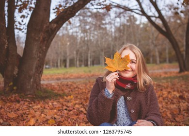 Woman hold yellow leaf in autumn park or forest