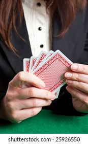 Woman holding 5 red cards about to place a card on the table