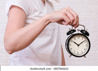 Woman holding an alarm clock showing 10 oclock, people should value and appreciate time, deadline concept.