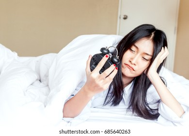 Woman holding alarmclock on the bed at the morning