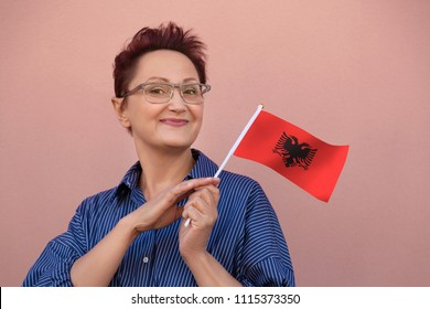 Woman holding Albania flag. Nice portrait of middle aged lady 40 50 years old with a national Albanian flag over wall background.Learning Albanian language. Visit Albania concept.