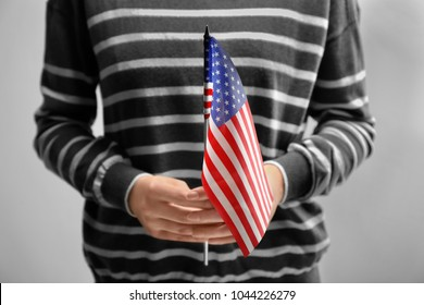 Woman holding American flag on light background. Immigration to USA
