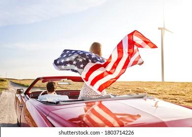 Frauen, die eine amerikanische Flagge auf einer Straßenreise führen