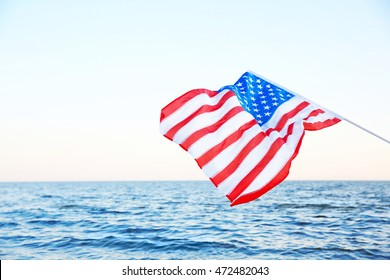 Woman holding American flag on beach