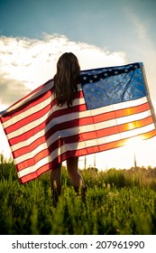 Woman holding American Flag in sunlight
