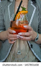 Woman holding Aperol cocktail in her hands in restaurant. Cocktail close up