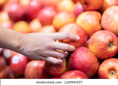woman holding apple to choose fresh apple best fruit for good health in bunch and buying in supermarket