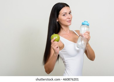 Woman holding apple and water bottle
