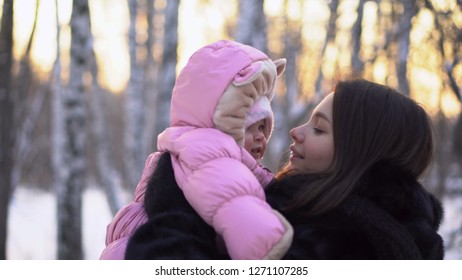 Woman holding baby in jumpsuit in outdoors. Close-up of young woman with baby in pink jumpsuit on background of winter grove with sunset