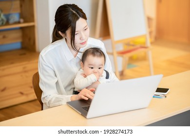 A woman holding a baby and operating a laptop