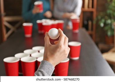 Woman holding ball for Beer Pong game