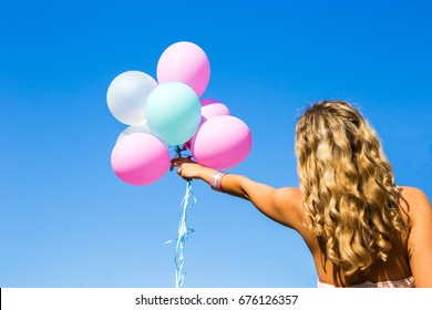 Woman holding balloons. Sky background