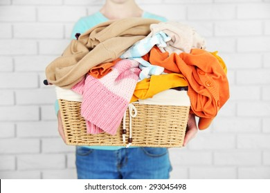 Woman holding basket with heap of different clothes, on bricks wall background