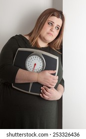 Woman holding a bathroom scale is leaning against wall with sad expression.