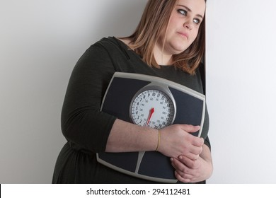 Woman holding a bathroom scale is leaning against wall with sad expression