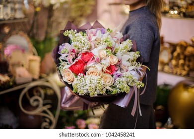 Woman holding a beautiful big bouquet of red and beige roses and other flowers wrapped in a purple paper