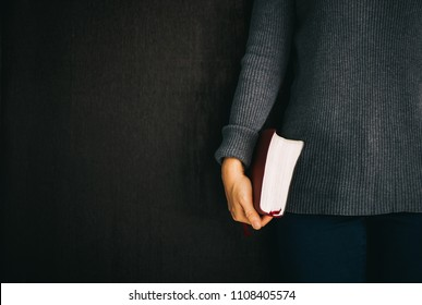 Woman holding the bible in hands on black with copy space.