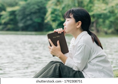Woman holding a Bible, a natural background, is faithful to God and love God's word