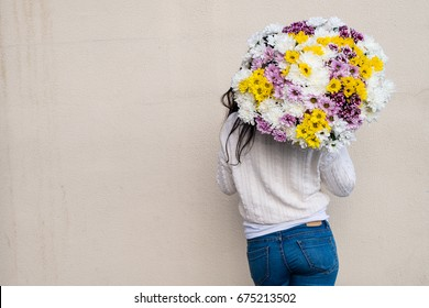 woman holding big beautiful bouquet of orange, white, pink and bright pink chrysanthemums, outdoors. Symbol of Mothers Day and Valentines Day