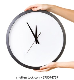 Woman holding a big clock isolated on a white background. Time concept