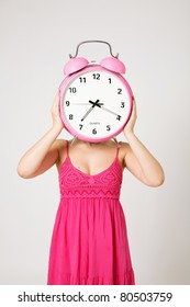 Woman holding big pink clock on head on white background