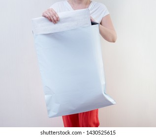 Woman holding big Poly plastic mailer mailing envelope