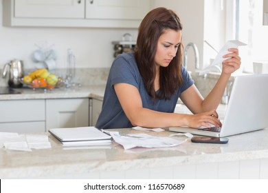 Woman holding a bill while calculating on the laptop