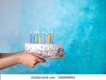 Woman holding birthday cake with burning candles on light blue background, closeup. Space for text