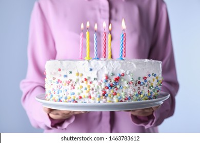 Woman holding birthday cake with burning candles, closeup