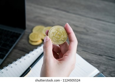 Woman holding a Bitcoin in her hand. Cryptocurrency investors concept.