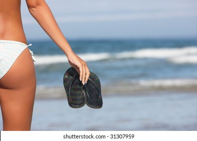 woman holding black flops on the shoreline