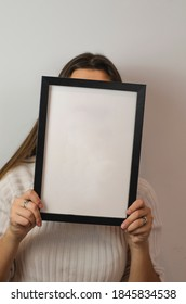 woman holding black photo frame with white background