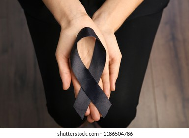 Woman holding black ribbon, closeup. Funeral symbol