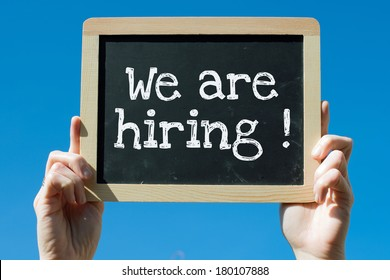 Woman holding blackboard with text We are hiring !