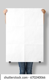 Woman holding a blank A0 poster mockup isolated on a gray background.