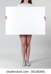 Woman holding a blank A1 poster