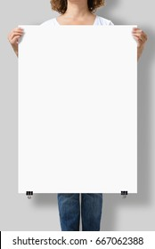 Woman holding a blank A1 poster mockup isolated on a gray background.