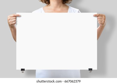 Woman holding a blank A2 poster mockup isolated on a gray background.