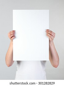 Woman holding a blank A3 poster