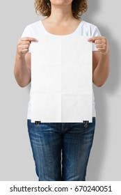 Woman holding a blank A3 poster mockup isolated on a gray background.