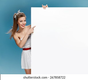 Woman holding a blank billboard on blue background / photo set of young American pin-up model on blue background with space for text