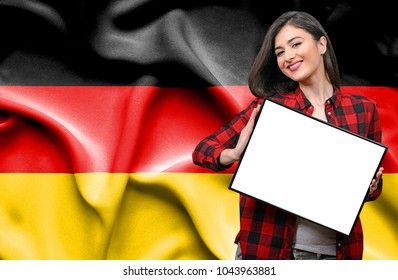 Woman holding blank board against national flag of Germany