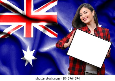Woman holding blank board against national flag of Australia