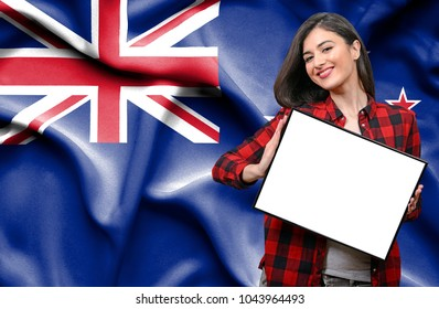 Woman holding blank board against national flag of New Zealand